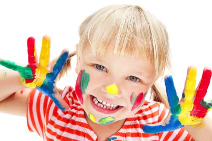 Uśmiechnięte dziecko z pomalowanymi kolorowo dłońmi