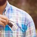 Mężczyzna chowa do kieszeni wizytówkę , na której widać taśmy filmowe i logo NetFactory.