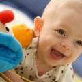 Uśmiechnięte dziecko na łóżku z zabawkami
