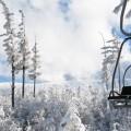 Wyciąg krzesełkowy na tle ośnieżonych stoków Karkonoszy i bajkowo obklejonych śniegiem choinek